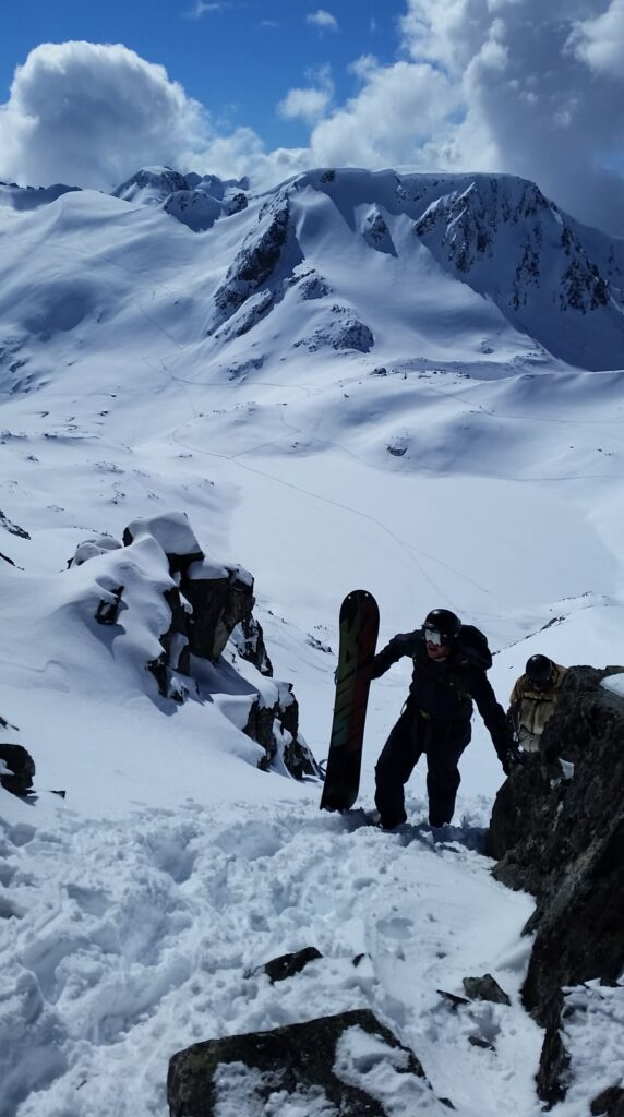 snowboarder cresting a ridge hiking in the mountains